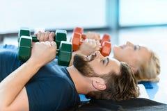 Gente joven de la aptitud que ejercita con pesas de gimnasia en el estudio de la aptitud Foto de archivo