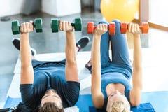 Gente joven de la aptitud que ejercita con pesas de gimnasia en el estudio de la aptitud Imágenes de archivo libres de regalías