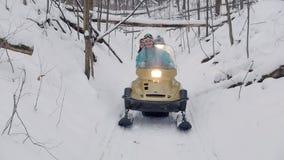 Gente joven del bosque del invierno en las motos de nieve que van abajo del camino en una pista especial almacen de metraje de vídeo
