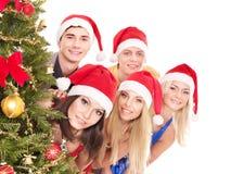 Gente joven del grupo por el árbol de navidad. Imagen de archivo libre de regalías