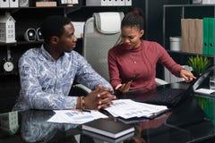 Gente joven del negocio del funcionamiento afroamericano de la nacionalidad con los documentos y el teléfono en la tabla en ofici imagen de archivo libre de regalías