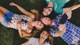 Gente joven descuidada que tiene una risa al aire libre que miente en hierba Imágenes de archivo libres de regalías