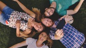 Gente joven descuidada que tiene una risa al aire libre que miente en hierba Fotografía de archivo libre de regalías