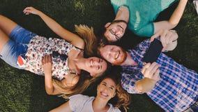 Gente joven descuidada que tiene una risa al aire libre que miente en hierba Foto de archivo libre de regalías