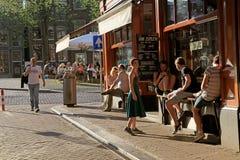 Gente joven en café al aire libre en el centro histórico de Amsterdam Fotografía de archivo libre de regalías