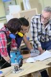 Gente joven en el entrenamiento de la carpintería con el profesor Imagen de archivo libre de regalías