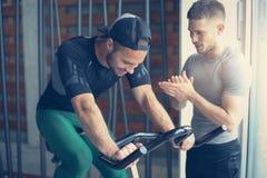 Gente joven en gimnasio Entrenamiento de los amigos al gimnasio y usar el teléfono elegante Fotografía de archivo