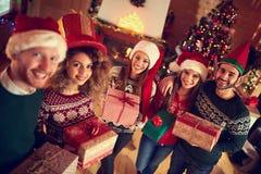 Gente joven en la Navidad con los regalos Imagen de archivo