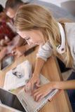 Gente joven en la sala de clase que trabaja en lapotp Imagenes de archivo