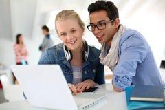 Gente joven en la universidad que trabaja en el ordenador portátil Imagen de archivo libre de regalías