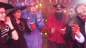 Gente joven en los equipos de Halloween que bailan en un pub almacen de video