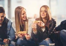 Gente joven en ropa casual que come la pizza Fotografía de archivo