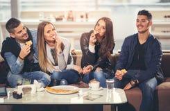 Gente joven en ropa casual que come la pizza Fotos de archivo