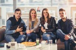Gente joven en ropa casual que come la pizza Imagen de archivo