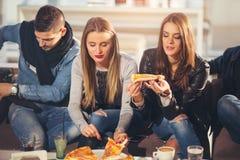 Gente joven en ropa casual que come la pizza Fotos de archivo libres de regalías