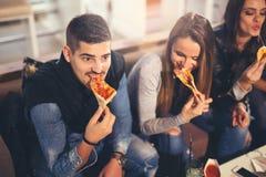 Gente joven en ropa casual que come la pizza Foto de archivo