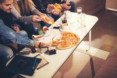 Gente joven en ropa casual que come la pizza Imagen de archivo libre de regalías