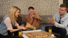 Gente joven en ropa casual que come la pizza, hablando, riendo Fotografía de archivo libre de regalías