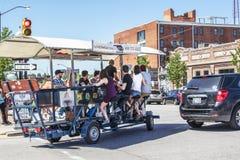Gente joven en una barra de la bici donde ayudan a la bicicleta del conductor el vehículo a través de las calles mientras que ten imagen de archivo