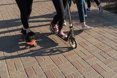 Gente joven en vaqueros y zapatillas de deporte que patinan y que usan una vespa en un pavimento concreto del ladrillo fotografía de archivo