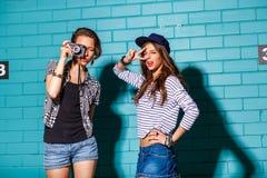 Gente joven feliz con la cámara de la foto que se divierte delante del azul Imagenes de archivo