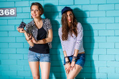 Gente joven feliz con la cámara de la foto que se divierte delante del azul Foto de archivo