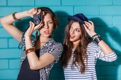 Gente joven feliz con la cámara de la foto que se divierte delante del azul Imágenes de archivo libres de regalías