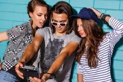 Gente joven feliz con la cámara de la foto que se divierte delante del azul Imagen de archivo libre de regalías