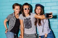 Gente joven feliz con la cámara de la foto que se divierte delante del azul Foto de archivo libre de regalías