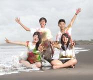 Gente joven feliz en una playa en verano con la cámara lenta y el concepto borroso Foto de archivo libre de regalías