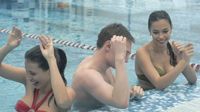 Gente joven feliz que baila en la piscina almacen de metraje de vídeo