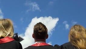Gente joven feliz que celebra la graduación, sombreros académicos que lanzan para arriba en aire almacen de metraje de vídeo