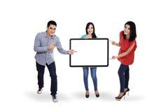 Gente joven feliz que lleva a cabo el cartel en blanco Imágenes de archivo libres de regalías