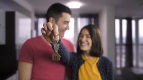Gente joven feliz que lleva a cabo llaves al nuevo hogar almacen de metraje de vídeo