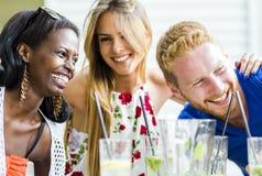 Gente joven feliz que ríe un feliz en una tabla Imágenes de archivo libres de regalías