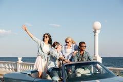 Gente joven feliz que ríe y que conduce el coche Imágenes de archivo libres de regalías