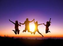 gente joven feliz que salta en la montaña Imagenes de archivo