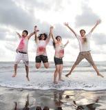 Gente joven feliz que salta en una playa en verano con la cámara lenta y el concepto borroso Foto de archivo libre de regalías