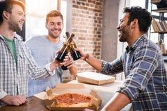Gente joven feliz que se divierte con la cerveza y la pizza en casa imagenes de archivo