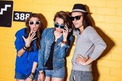 Gente joven feliz que se divierte delante de la pared de ladrillo amarilla Fotos de archivo