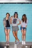 Gente joven feliz que se divierte delante de la pared de ladrillo azul Fotografía de archivo libre de regalías