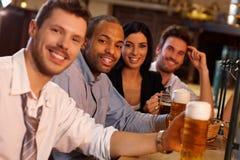 Gente joven feliz que se sienta en el pub, cerveza de consumición fotos de archivo