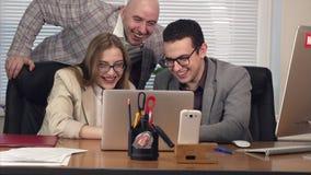 Gente joven graciosamente feliz - hombres y mujeres - en la oficina, mirando el ordenador portátil y la risa almacen de metraje de vídeo