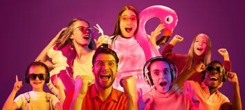 Gente joven hermosa en la luz de ne?n aislada en fondo rosado del estudio foto de archivo