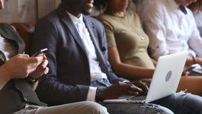 Gente joven multirracial insociable que usa los ordenadores portátiles y los teléfonos que comunican en línea almacen de video