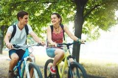 Gente joven, pares con las bicicletas en el parque Imagen de archivo
