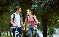 Gente joven, pares con las bicicletas en el parque Fotografía de archivo
