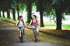 Gente joven, pares con las bicicletas en el parque Imagen de archivo libre de regalías
