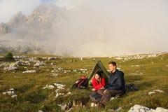 Gente joven que acampa en las montañas en niebla Imagenes de archivo