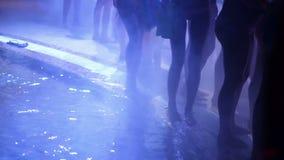 Gente joven que baila en el humo en club nocturno metrajes